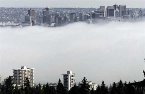 The buildings of downtown Vancouver, Canada, and apartment buildings of the North Shore rise above an afternoon fog over ther harbour.