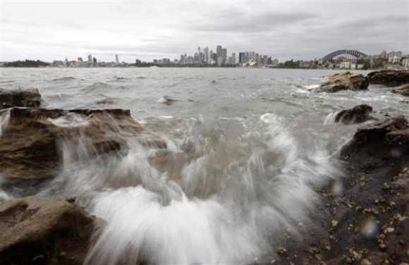 Waves wash over rocks that fringe Sydney Harbour.