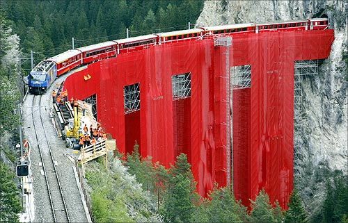 Red cloth veils the scaffoldings at the renovation site of the Landwasserviadukt bridge as a train crosses near the eastern Swiss town of Filisur.