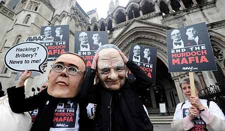 Protesters dressed as James and Rupert Murdoch outside a London court.