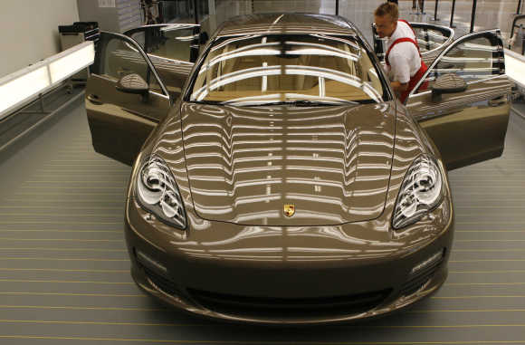 Workers of Porsche Automobil Holding SE assemble Panamera model at the production line in Leipzig, Germany.