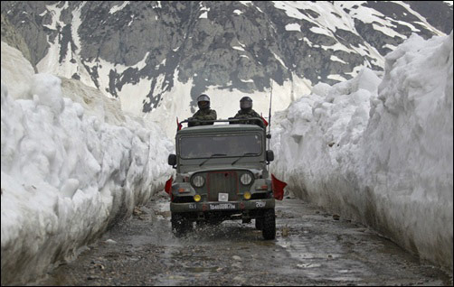 Indian army soldiers travel in a vehicle on a mountainous road covered by snow after the Srinagar-Leh highway was opened.