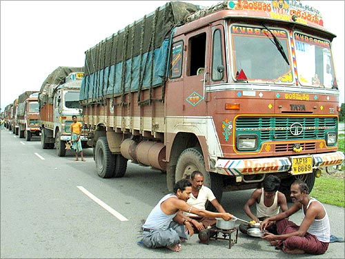Indian truck drivers cook a meal along a highway near Boksher village.