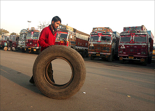 A helper rolls a tyre near the parked trucks during a strike by truckers in Chandigarh.