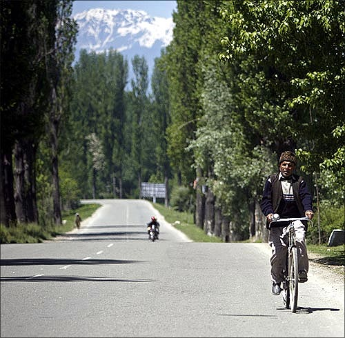 A man rides a bicycle on a deserted highway, north of Srinagar.