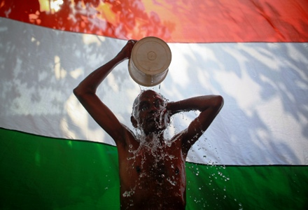 A man takes a bath outside his shanty in front of the Indian national flag in Dharavi, one of Asia's largest slums, in Mumbai.
