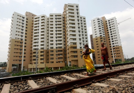 Woman carrying a child walks ahead of her husband on a railway track in front of residential buildings under construction on the outskirts of Kolkata.