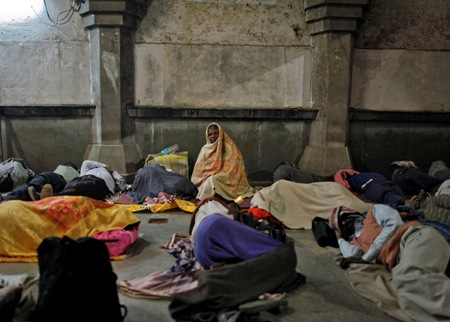 Commuters rest outside the ticket counter at a railway station in the old quarters of Delhi.