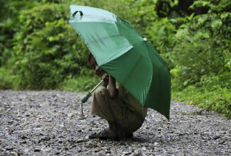 A boy reacts to the camera during a monsoon shower in a village in Uttarakhand