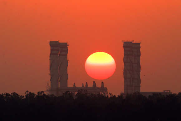 Sun sets behind chimneys of a thermal power station in New Delhi.