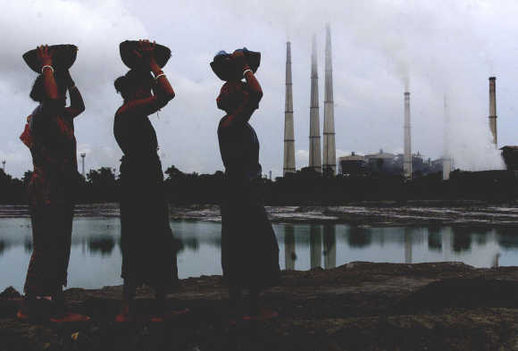 Labourers carry small pieces of coal deposit from liquid ash generated from a thermal power plant (background) in Kolaghat, 75km west of Kolkata.