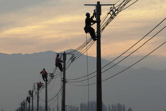 Workers repair electricity pylons and wires in a rural area near Santiago.