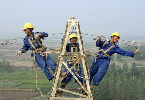 Labourers repair electricity cables on a power tower in Chuzhou, China.