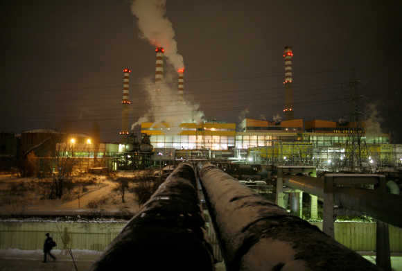 Man passes by pipes coming out of Druzhba thermal power station in Sofia.