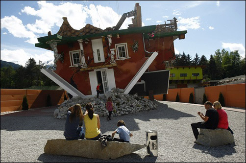People sit in front of a house, which was built upside down by Polish architects Glowacki and Rozanski, in the western Austrian village of Terfens.