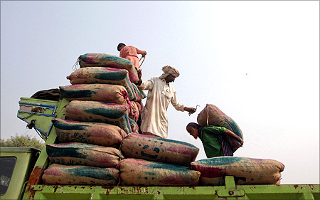 Men load sacks of dates onto a truck at a dry port before transporting them to India at Wagah border.