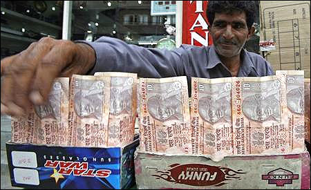 A Kashmiri money changer Nissar Ahmad displays newer Indian rupee notes in Srinagar on July 21, 2008.