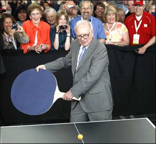 Berkshire Hathaway chairman Warren Buffett plays table tennis using a giant paddle.