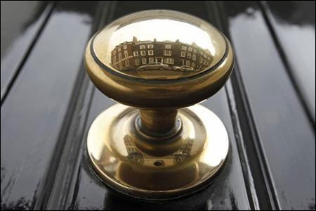 Houses are reflected in a door knob on a street in London.