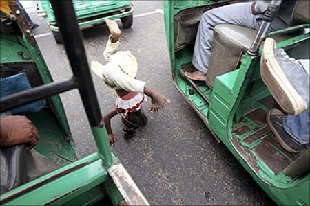 A girl street performer does a headstand at a traffic signal in New Delhi.