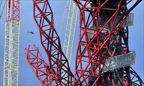 A helicopter flies near the Anish Kapoor designed ArcelorMittal Orbit tower at the Olympic site at Stratford in east London.