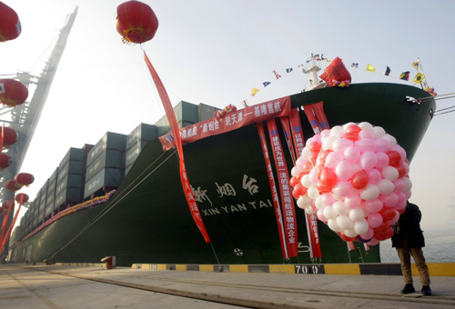 A man holding balloons stands next to a ship leaving to Keelung in Taiwan during a ceremony of the first direct sea transport across the strait, at Tianjin Port.