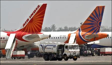 A fuel tanker moves past Air India passenger jets.