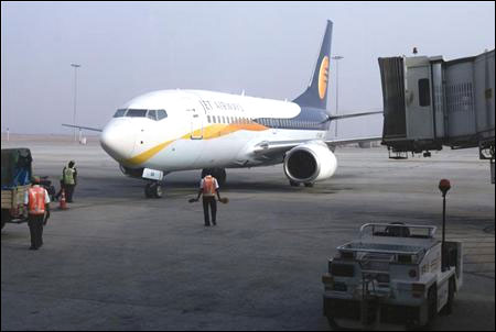 Ground staff guide a Jet Airways aircraft towards a gate on the tarmac at Bengaluru International Airport.