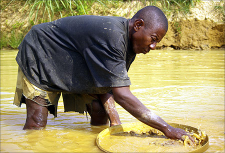 A miner washes muddy gravel in the hope of finding diamonds
