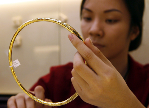 A woman displays gold for sale at a shop in Hanoi.