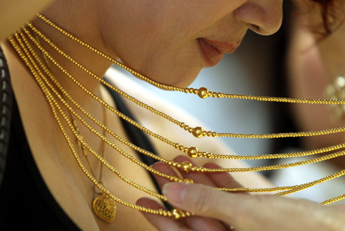 A customer tries on a gold necklace at a gold shop in Hanoi.