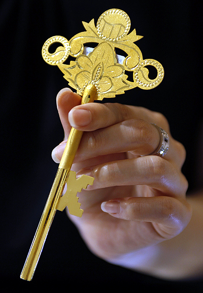 An employee holds a gold key during a photo opportunity at a jewellery shop in Seoul.
