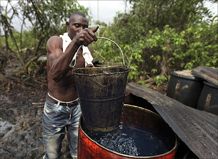 A man collects crude oil from a drum at an illegal refinery in the village of Isuini-biri in Nigeria's Bayelsa state.