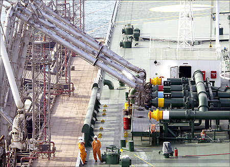 Kuwait Oil Tanker employees oversee the loading of crude oil into the new Kazimah III Oil Tanker at Ahmadi North Pier in Kuwait.