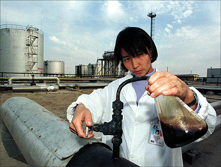 A Kazakh specialist takes crude oil for analysis at the Kumkol oil field near western Kazakh city Kuzul-Orda in this September 1997 file photo.