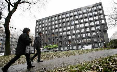 Pedestrians walk past the Riksbank building in downtown Stockholm, Sweden