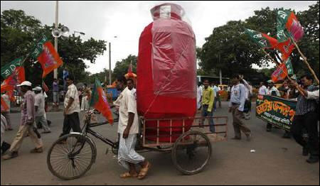 A man pulls a rickshaw loaded with a mock cooking gas cylinder.