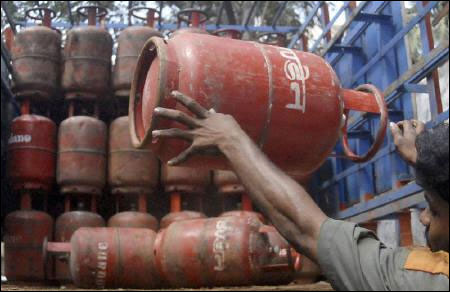 An employee from a gas agency loads a cooking gas cylinder onto a truck in Chennai.