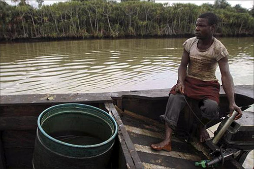 A labourer operates the engine of a locally built canoe, which contains a plastic drum used in siphoning crude oil for illegal refinery, along the Diebu creek in Nigeria's Bayelsa state May 15, 2012.