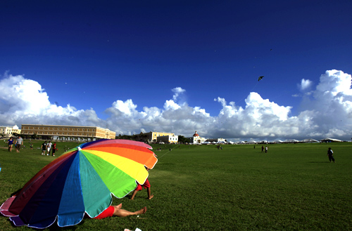 A family flies a kite in front of the Fort San Felipe del Morro