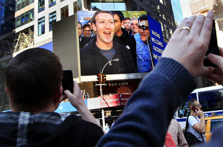 Facebook Inc. CEO Mark Zuckerberg is seen on a screen televised from their headquarters in Menlo Park moments after their IPO launch in New York.