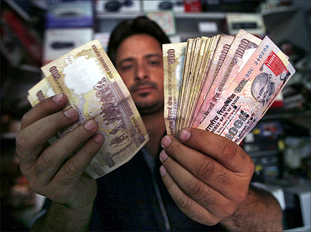 A shopkeeper poses for a picture as he counts Indian currency notes at his shop in Jammu.