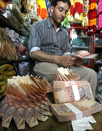 A Kashmiri shopkeeper makes a garland of Indian currency notes inside his shop in Srinagar.