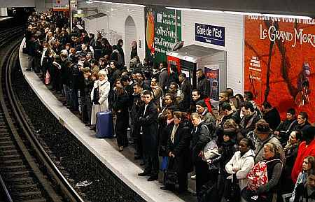 Commuters wait for a train at a metro station in Paris