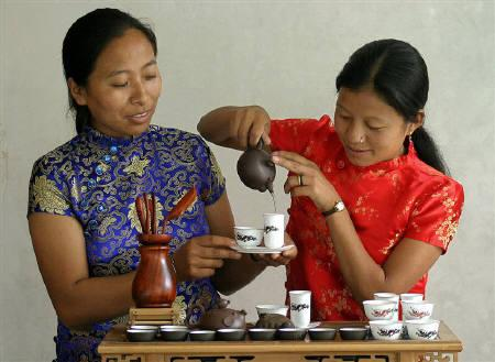 A tea garden worker (R) pours tea inside a tea garden estate in Siliguri.