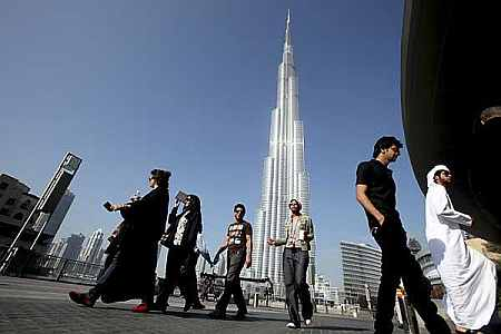 A group of Emiratis walk past the Burj Dubai Tower