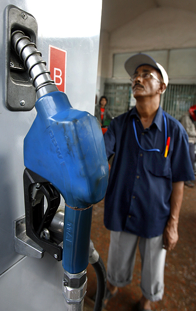 An attendant looks at the price board at a petrol station in Dhaka.