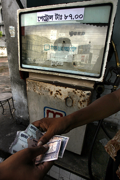 A station attendant receives money from a customer after filling up a car at a petrol station in Dhaka.