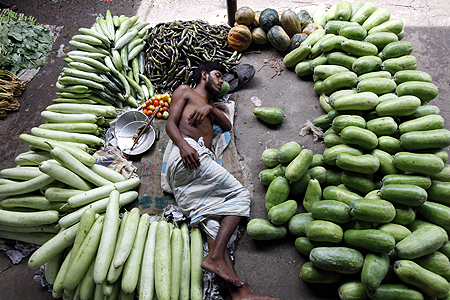 A vegetable vendor takes a nap during a hot summer afternoon at Karwanbazar in Dhaka.