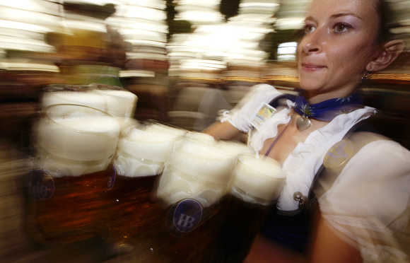 A waitress carries the traditional one-litre beer mugs at the opening of the Munich Oktoberfest.